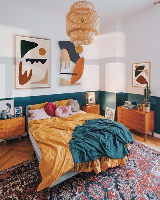 a colorful mid-cenntury modern bedroom with white and teal color block walls, an upholstered bed, stained furniture, colorful bedding and colorful artworks