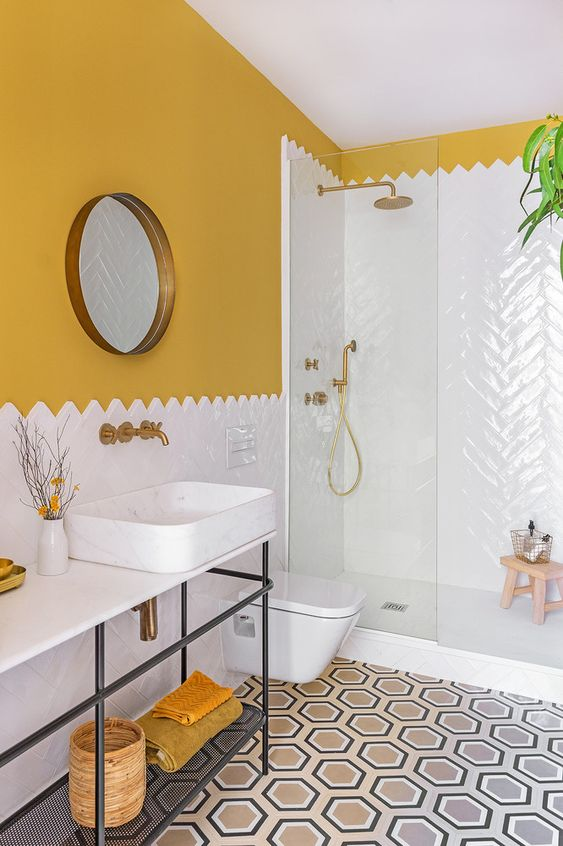 a colorful mid-century modern bathroom with mustard walls, a mosaic tile floor, a white tile shower space and mustard towels