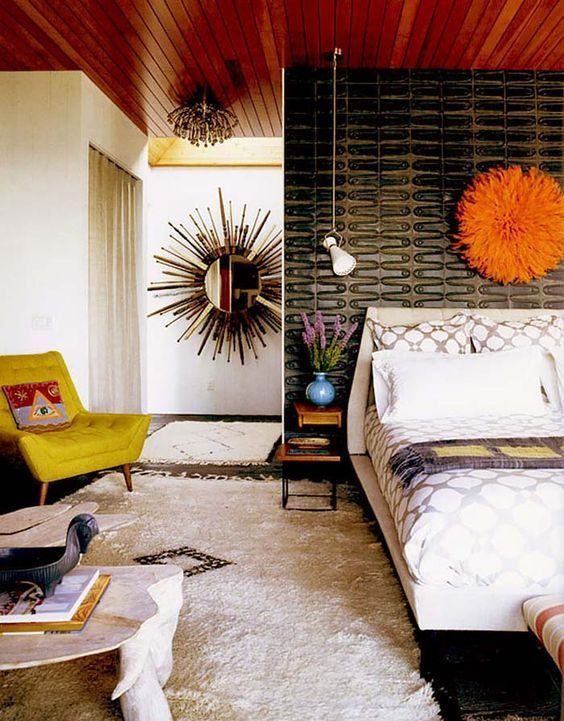 a colorful mid-century modern bedroom with a black patterned wall, a white upholstered bed, a mustard chair, a low coffee table, a mirror
