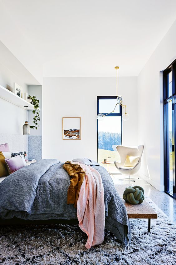a colorful mid-century modern bedroom with a view, a bed with colorful bedding and a printed rug, potted greenery and a chic chandelier