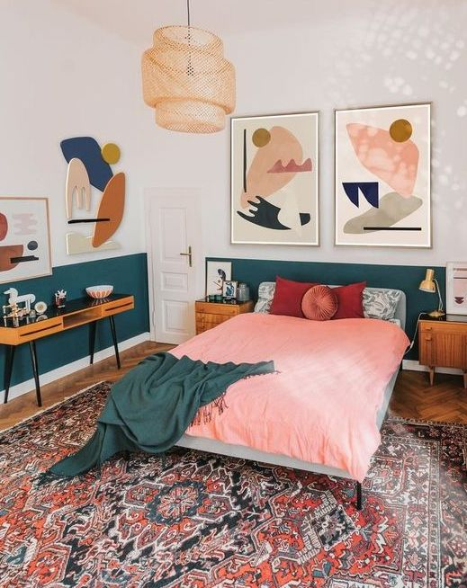 a colorful mid-century modern bedroom with an upholstered bed and stained furniture, colorful bedding, a printed rug, colorful artworks