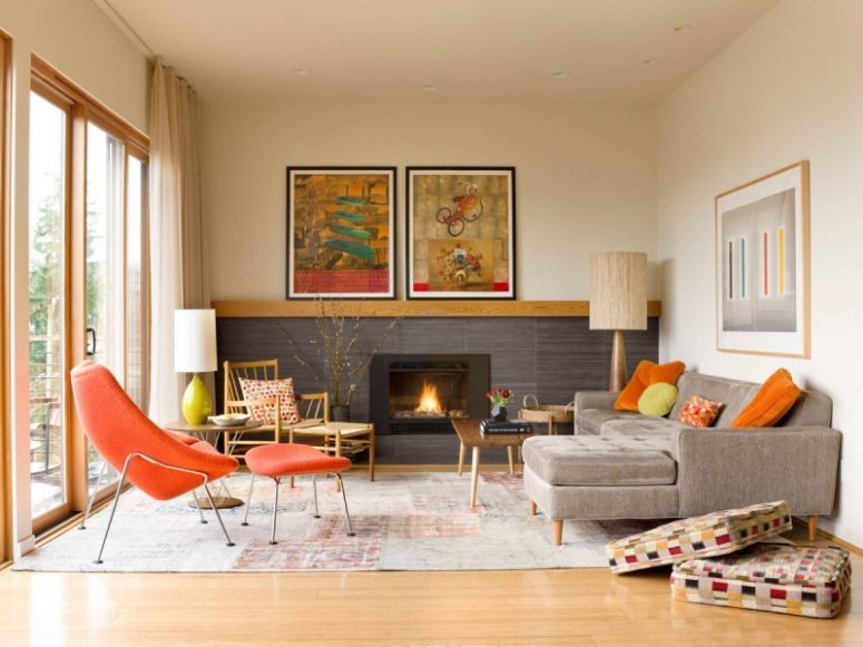 a colorful mid-century modern living room with a built-in fireplace, a grey sectional, a fiery red chair, a wooden chair, a low table and colroful artworks