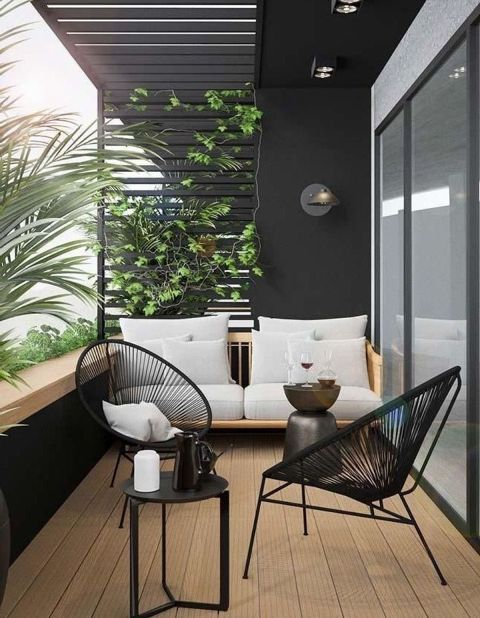 a contemporary balcony with wooden and rattan furniture, a metal coffee table, greenery interweaving a planked screen