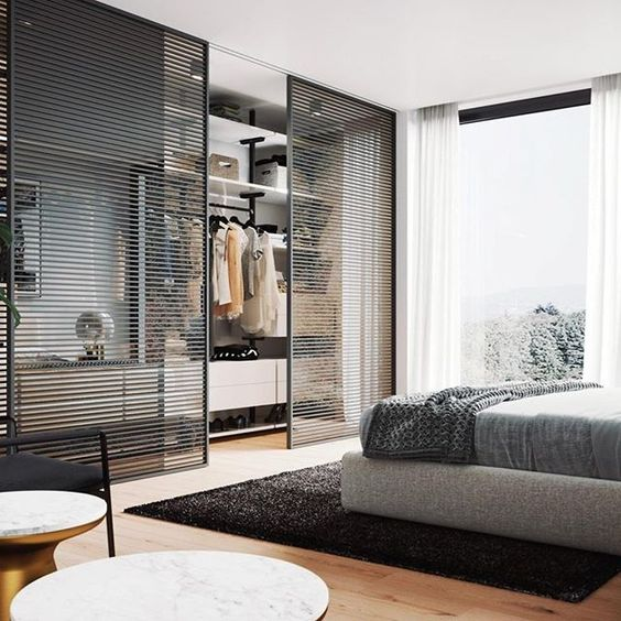 a contemporary bedroom done in grey and black, with light-stained wood, and with a closet with black wood slab sliding doors is cool