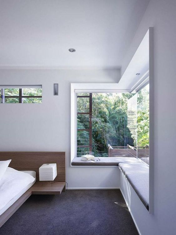 a contemporary bedroom with a floating bed and floating nightstands, a large corner window with a built in daybed for reading here