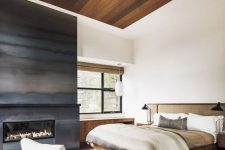a contemporary bedroom with a natural feel, a metal fireplace, a stained wood ceiling, a wooden and rattan bed, a wooden desk and a grey chair