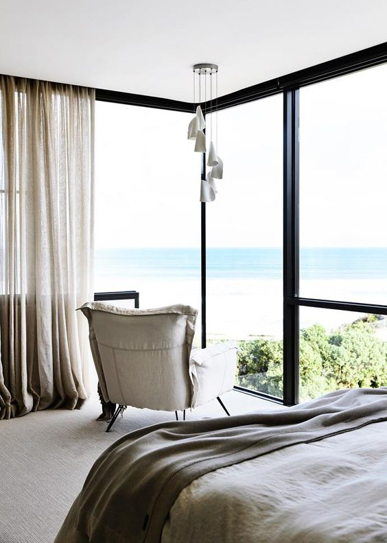 a contemporary bedroom with a neutral chair, a bed with neutral bedding and curtains plus a corner window to enjoy the sea views