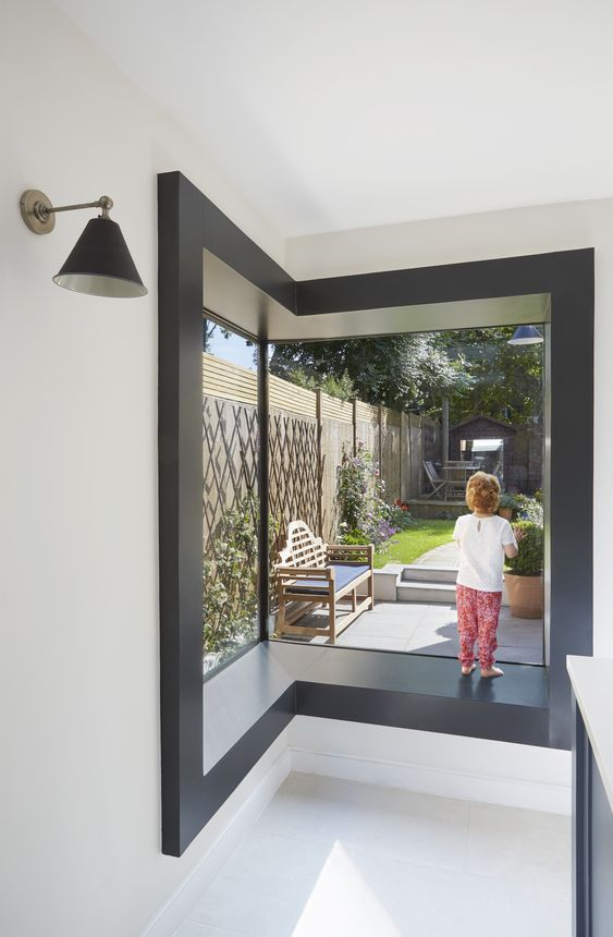a contemporary corner window with a black windowsill and a cool view of the backyard is a lovely idea to use it as a seat and to enjoy the views