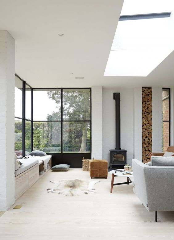 a contemporary living room with a skylight, a large corner window, a daybed, printed pillows and bedding and a black hearth