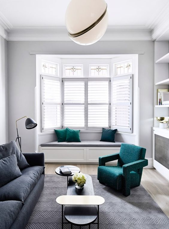 a contemporary living room with open shelves and storage units, with a bow window with a built-in daybed and pillows, a green chair and a grey sofa