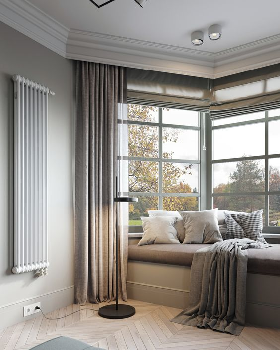 a contemporary neutral space done with a bow window, with a built-in windowsill bed, neutral and printed bedding and neutral curtains