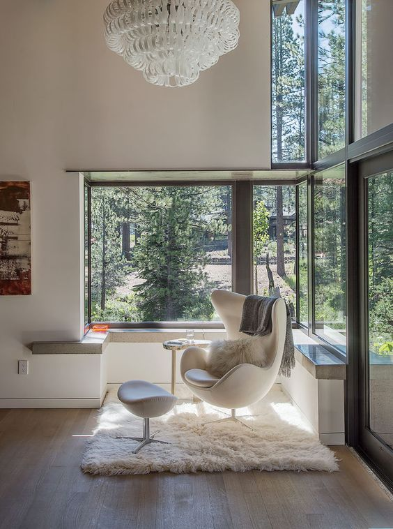 a contemporary nook with a large corner window, a creamy egg-shaped chair and a footrest and a chandelier