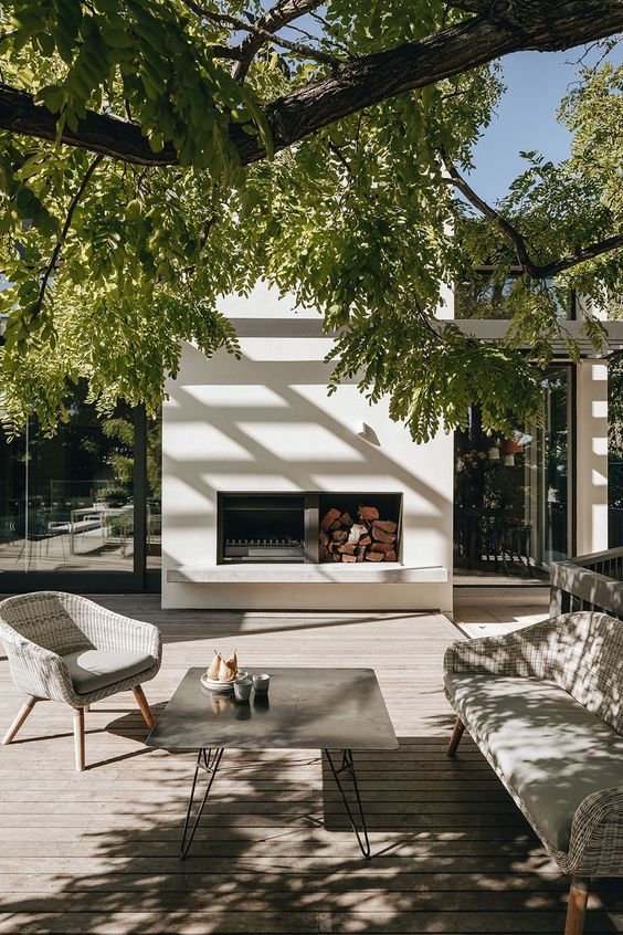 a contemporary terrace with a wooden deck, a fireplace, grey wicker furniture, a concrete coffee table and a tree is gorgeous