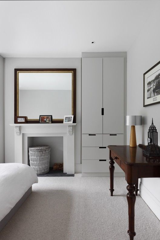 a contemporary white and grey bedroom with a built-in fireplace, a built-in wardrobe, a bed with neutral bedding, a dark stained narrow table