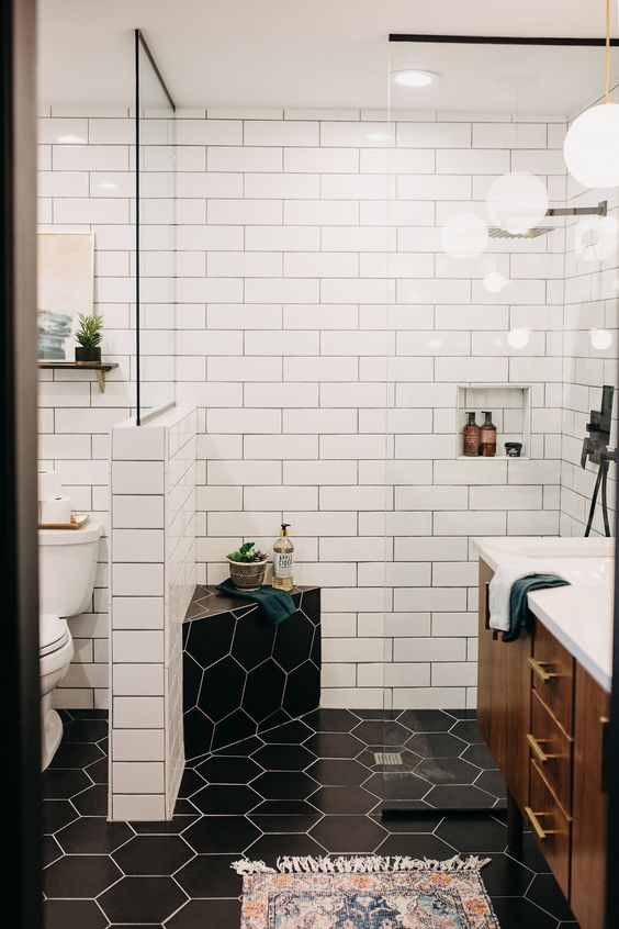 a contrasting black and white bathroom with white subway tiles and black hexagon ones, a stained vanity, black touches