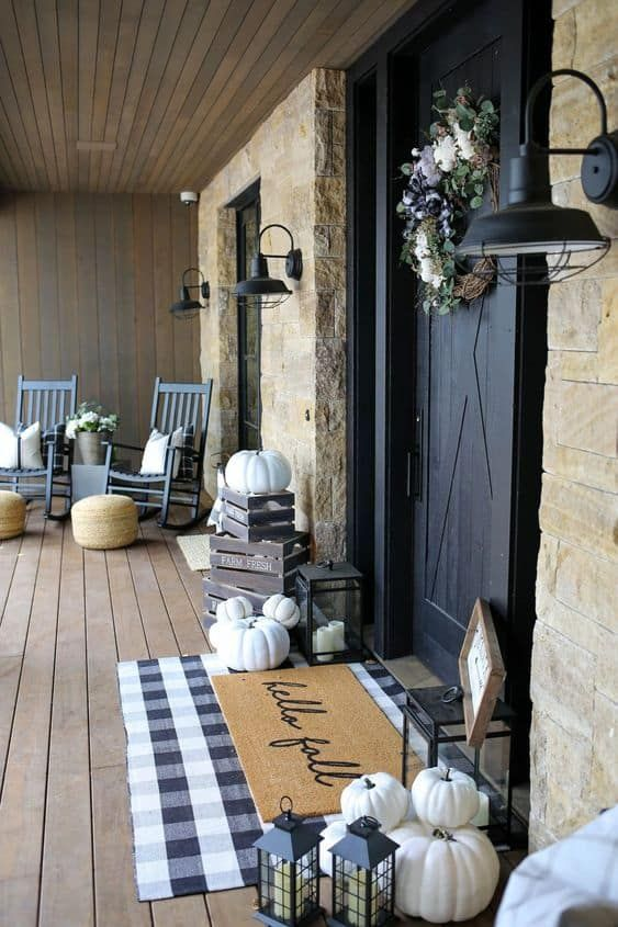 a contrasting farmhouse porch with black rockers, layered rugs, pumpkins in crates, candle lanterns and black sconces