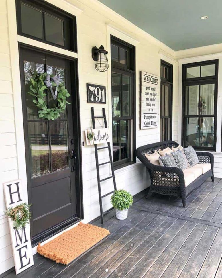 a contrasting rustic porch with a black door and deck, a black wicker sofa, a ladder, signs, potted greenery and sconces