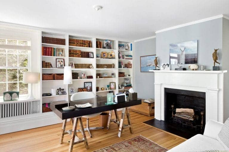 a cool and light-filled home office with built-in shelves, a fireplace, a black desk, a white sofa, some decor is very cool
