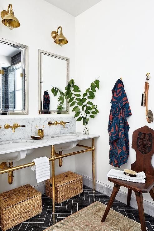 a cool bathroom with a gold sink stand, gold fixtures and sconces and mirrors in silver frames, a dark stained chair and basket boxes