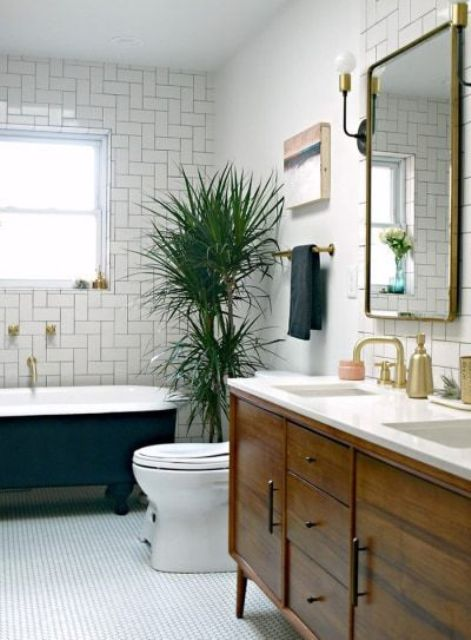 a cool mid-century modern bathroom with a black clawfoot tub, white tiles of various kinds, a stained vanity, a mirror and a potted plant