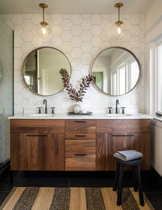 a cool mid-century modern bathroom with white hex tiles, a stained vanity, round mirrors, pendant lamps, a striped rug