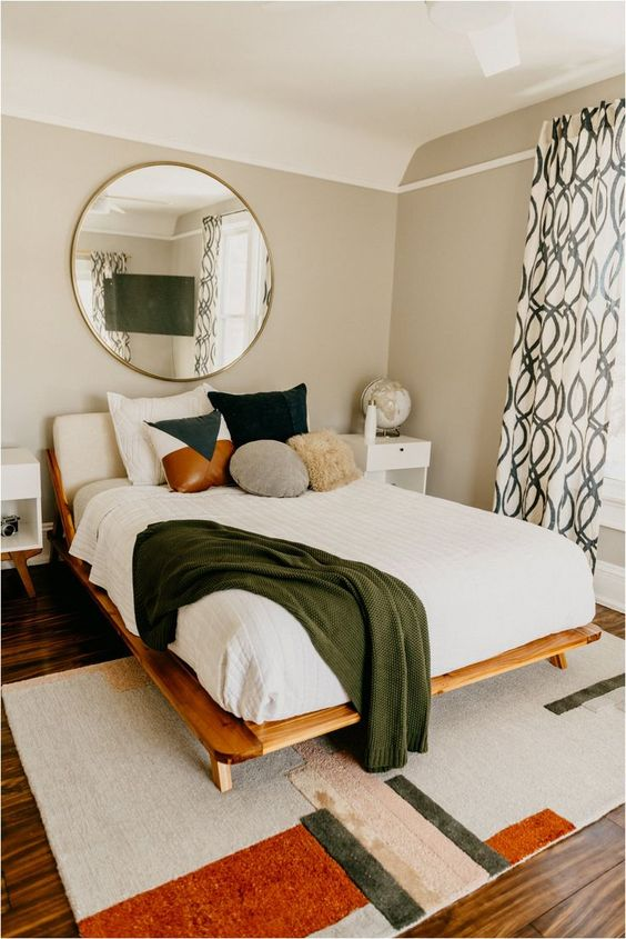 a cool mid-century modern bedroom with a bold geo rug, a wooden bed with colorful pillows, neutral nightstands and a round mirror over the bed