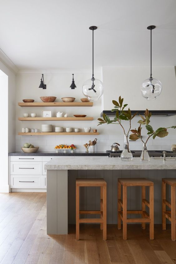 a cool mid-century modern kitchen with white shaker style cabinets, a large hood, a grey kitchen island, open shelves and cool lamps