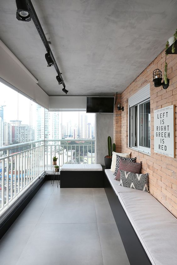 a cool modern balcony with a built-in upholstered bench along the whole wall, a small seat, potted plants and lamps