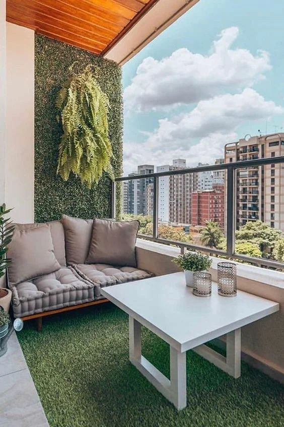 a cool modern balcony with a faux living wall and floor, a cool loveseat, potted greenery, a small table with greenery and candles