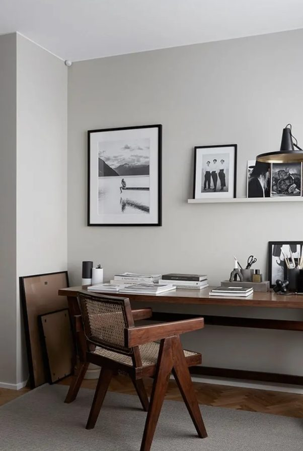 a cool modern home office with a dark stained desk, a matching chair with cane, a ledge gallery wall and black and white photos