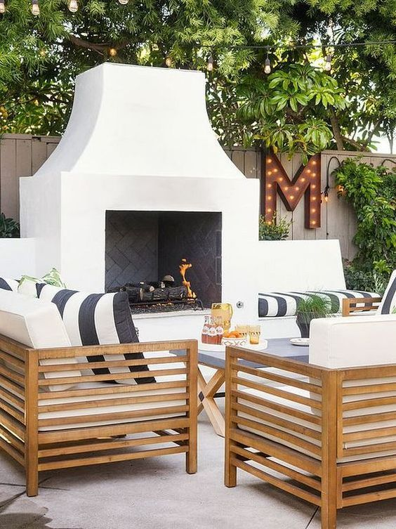 a cool modern terrace with a white fireplace, light stained furniture, black and white textiles, potted greenery and a marquee letter is amazing
