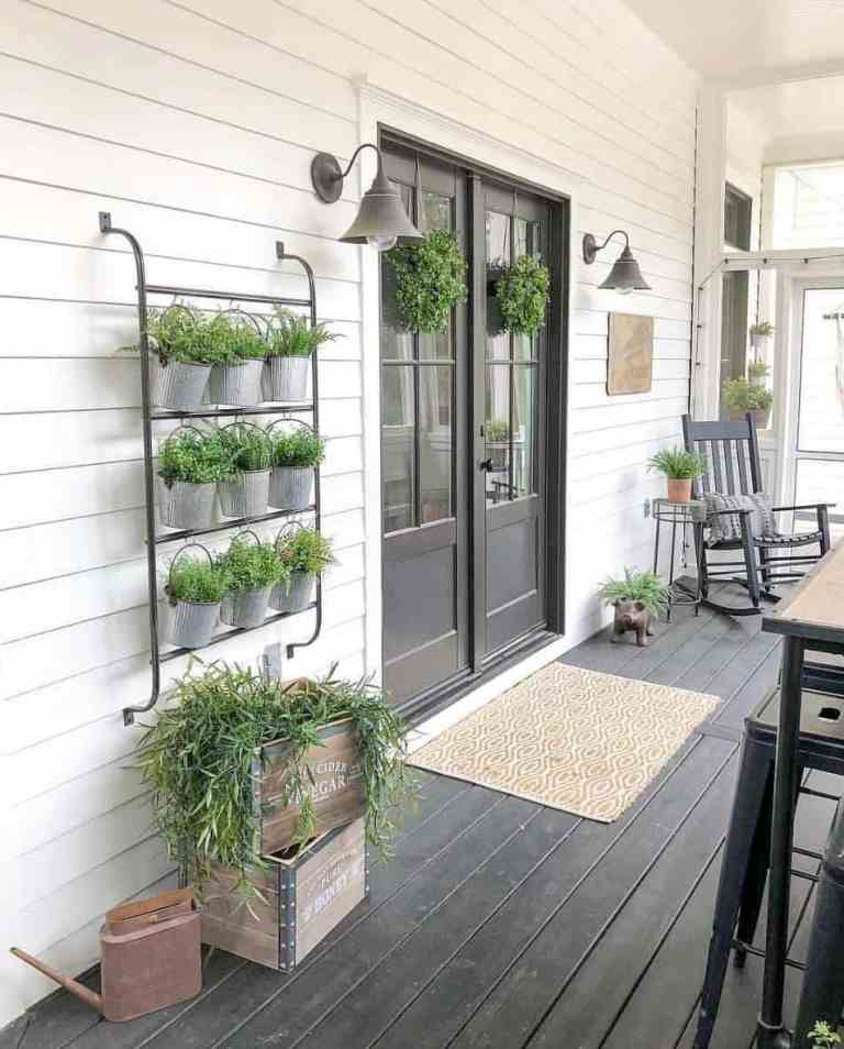 a cool rustic porch with a black deck, doors and furniture, potted greenery, sconces and crates plus a printed rug is lovely