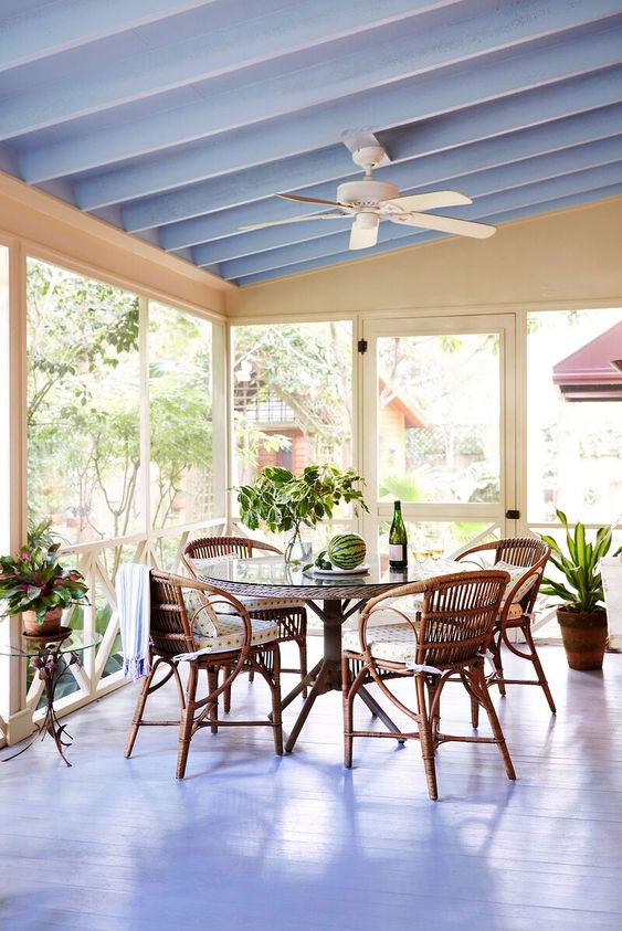 a cottage screened porch with a dining space made with rattan chairs and a round table, potted greenery and lovely views of the surroundings