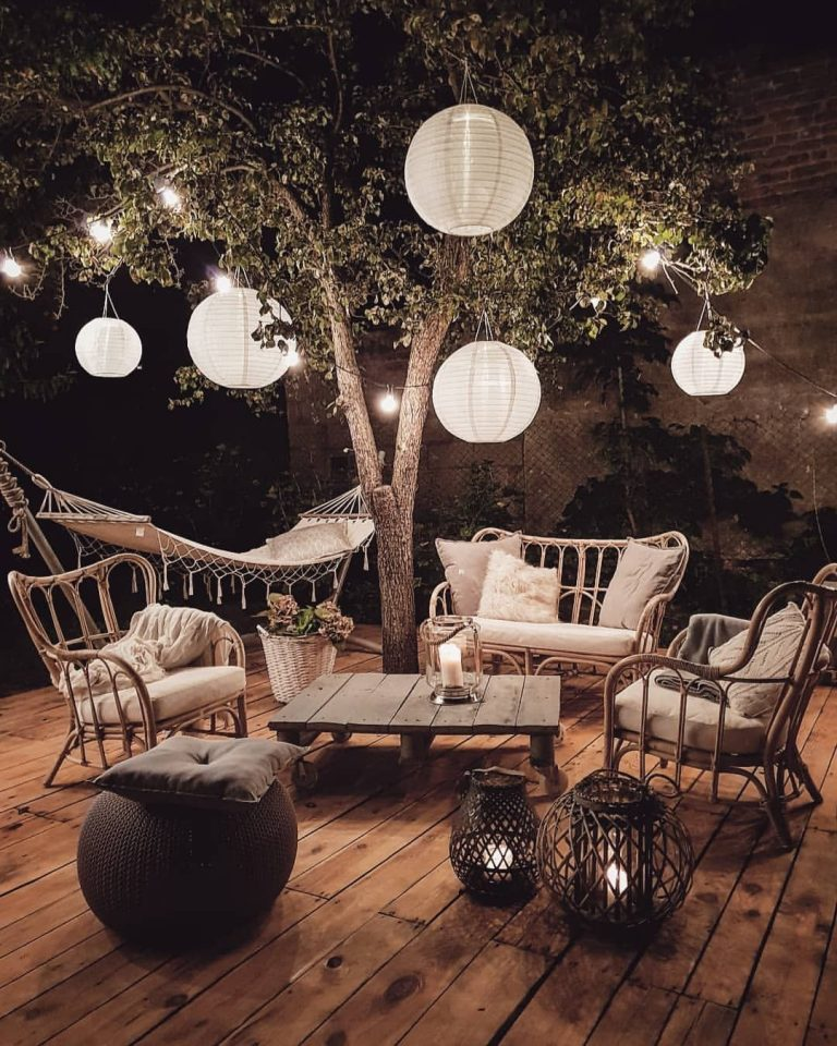 a cozy boho outdoor space with rattan furniture, a pallet table, woven candle lanterns, a small pouf and lots of paper lamps hanging around