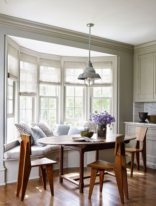 a cozy farmhouse nook with a bow window, a windowsill banquette seating, a wooden table and wooden chairs plus a retro lamp