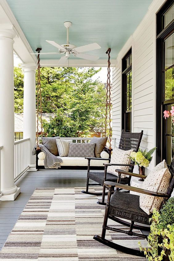 a cozy farmhouse porch with a black hanging daybed with lots of printed pillows, black rockers and lots of greenery