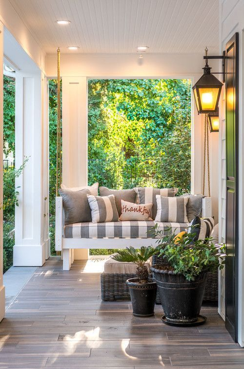 a cozy farmhouse porch with a hanging daybed with striped pillows, a wicker lounger, potted plants and blooms is a chic idea