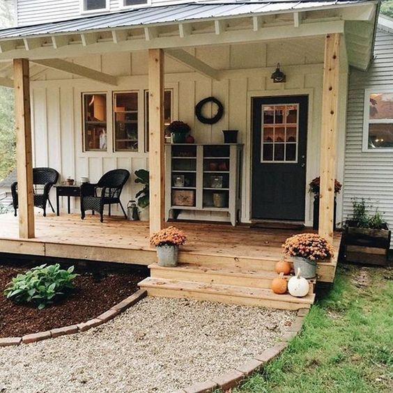 a cozy farmhouse porch with black chairs and a table, a neutral sideboard with accessories on display and potted blooms and pumpkins