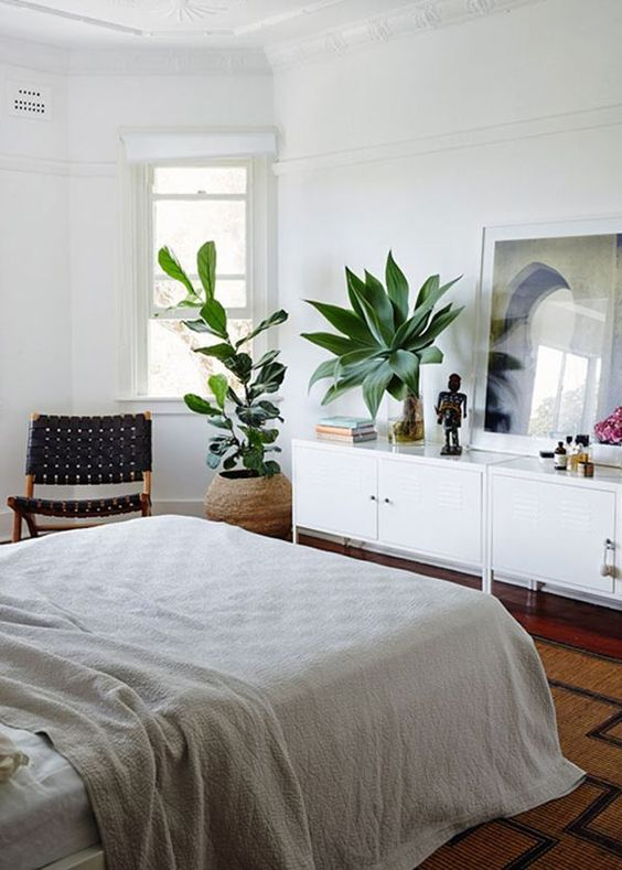 a cozy mid-century modern bedroom with a dark stained floor, a white storage unit, a bed with neutral bedding, statement plants and a black woven chair
