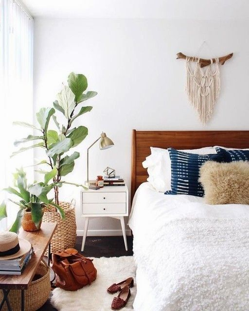 a cozy mid-century modern bedroom with a stained bed, neutral and navy bedding, baskets for storage and to cover pots, brass lamps and a bench