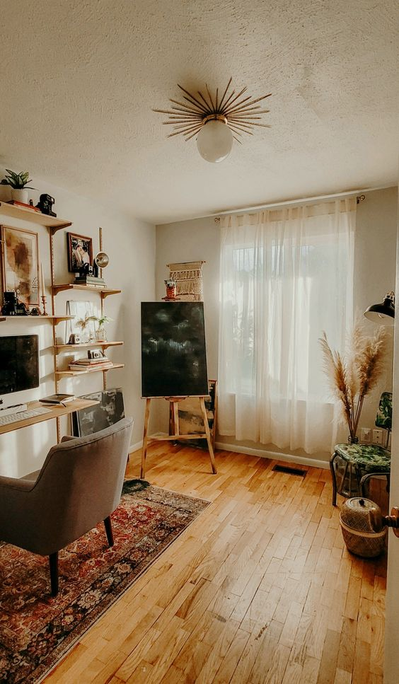 a cozy mid-century modern home office with a large shelf and desk wall unit, a comfy chair, a printed rug, some baskets and plants