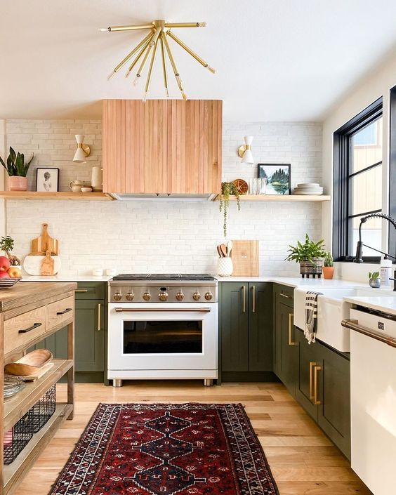 a cozy mid-century modern kitchen with green cabinets, light-stained shelves, a hood, white countertops, a wooden kitchen island