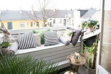 a cozy modern balcony with a white pallet bench, printed textiles, some greenery and blooms and a view of the roofs is a lovely space