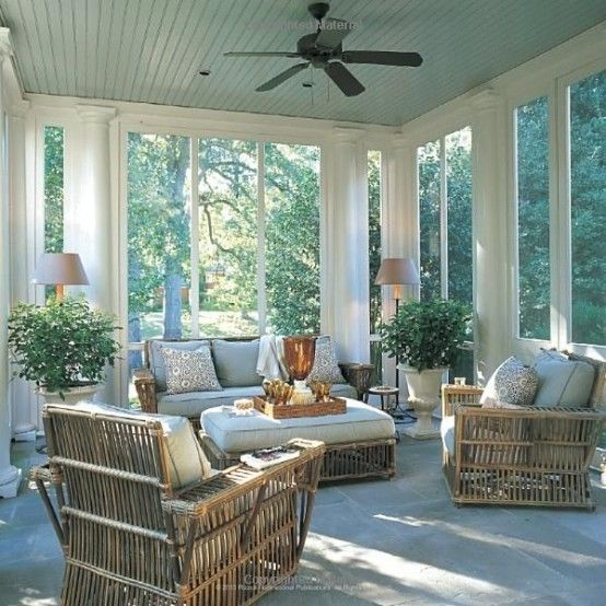 a cozy modern rustic screened porch with rattan furniture, potted plants, lamps and printed pillows is a lovely space