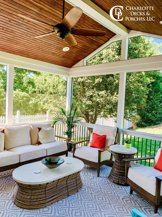 a cozy modern screened porch with chic stained and white upholstery furniture, rattan tables, colorful pillows and lovely views around