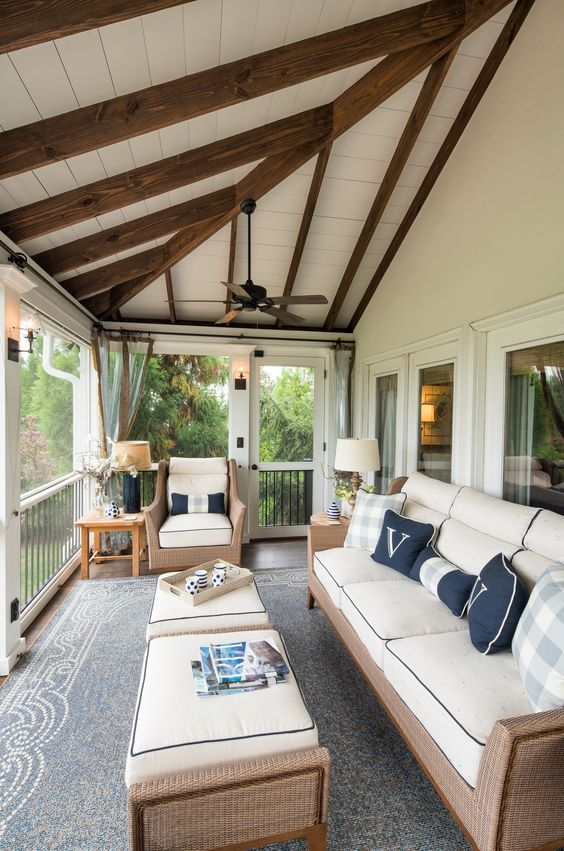 a cozy modern screened porch with neutral wicker furniture, blue pillows, side tables and some flowers is lovely