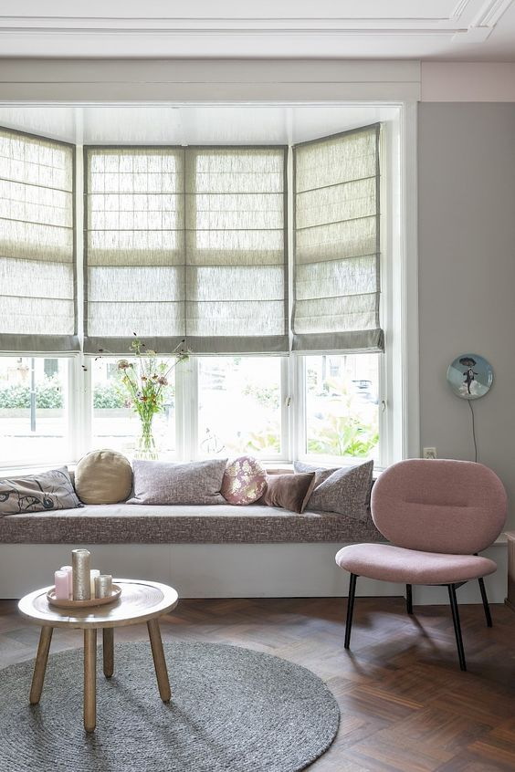 a cozy pastel interior with a bow window, a built-in windowsill daybed with pillows, a round rug and a pink chair