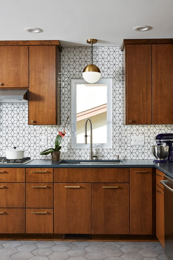 a cozy rich-stained kitchen with graphite grey stone countertops and white geometric tiles on the backsplash