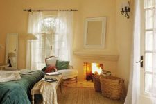 a cozy rustic bedroom with pastel yellow walls, a built-in fireplace, a bed with blue bedding, a bench and a vintage chair plus baskets