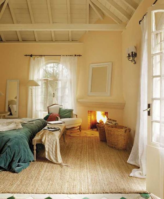 a cozy rustic bedroom with pastel yellow walls, a built in fireplace, a bed with blue bedding, a bench and a vintage chair plus baskets